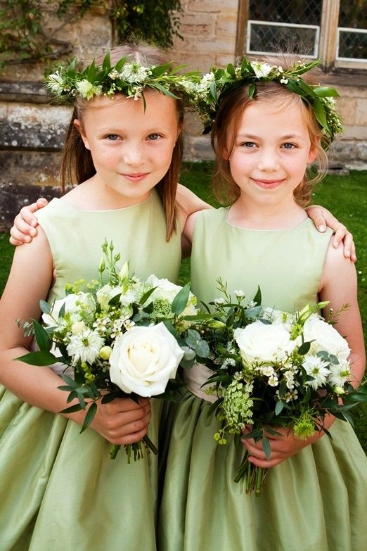 Sweet and simple green flower girl dresses with a white band.  Accented with greenery floral wreaths and carrying white and green bouquets