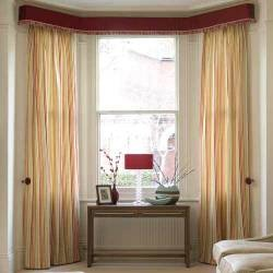 For a hotel-chic window treatment like this, choose striped satin for a tailored look and give the pelmet a touch of decorative detail with a fringe trim.  Use plain track in a bay so the curtains will run smoothly, but hide it away behind a stylish modern pelmet.