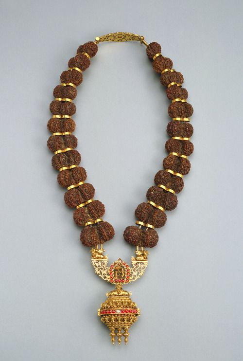 Garland of rudraksha seeds with figures of Parvati and Nandi on the clasp. Made in India in the late 19th-early 20th century (source).