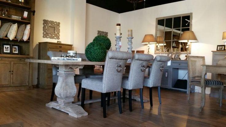 Stół i krzesła w nowoczesnym stylu. Prostokątny stół o monumentalnych nogach, stanowiących jego solidną podstawę. Stół mieszczący nawet 8 osób. Krzesła tapicerowane w kolorze szarym z prostymi nóżkami ale ozdobnym oparciem z pinami i uchwytem.