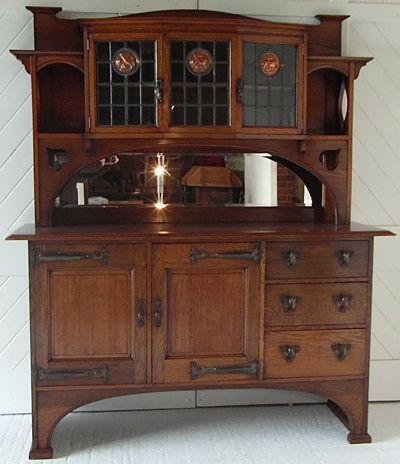 Arts & Crafts oak sideboard  with 3 leaded glass panels incorporating stylised copper roundels and cut out decoration.  Waring & Gillow (stamped drawer)  Circa 1900