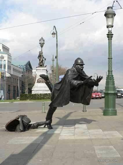 Amazing balance in this statue!  Man, manhole, caped man, foot caught, statue, art