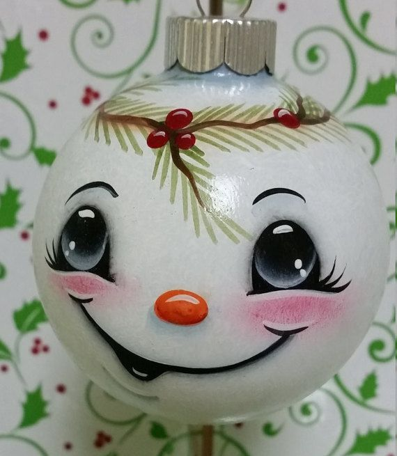 This Smiling Snowman looks upon all the activity going on in your home during the Holiday Season. He is made of glass and is 2 1/2 inches wide. He is free handed so although he may look similar to other ornaments he is always just a touch different which makes him very unique. He is painted with non-toxic paints and varnish so he is quite safe to handle, however as with all glass items handle with care. There are four different facial expressions to choose from. These little guys would be…