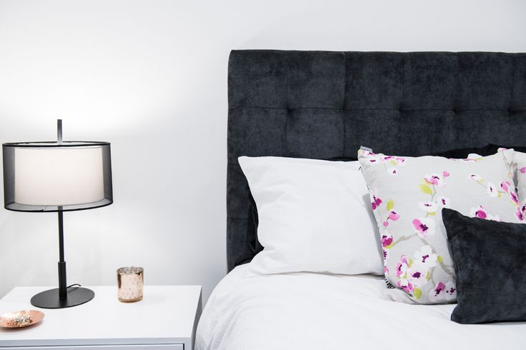 Bedroom design featuring upholstered charcoal bedhead with feature bedside lighting.