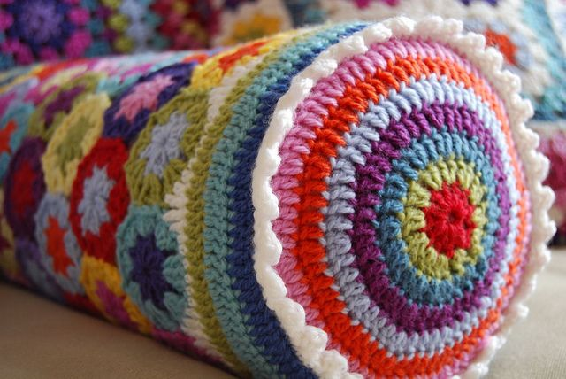 hexagon bolster pillow- hexagon motifs around body, striped rounds on circle end with little scallop border where the two meet