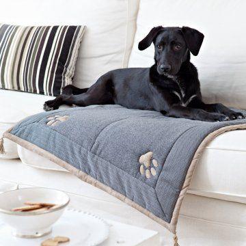 Glæsilegt hundateppi. Plaid matelassé pour chien en tissu gris avec empreintes de pattes appliquées et pompons aux quatre coins