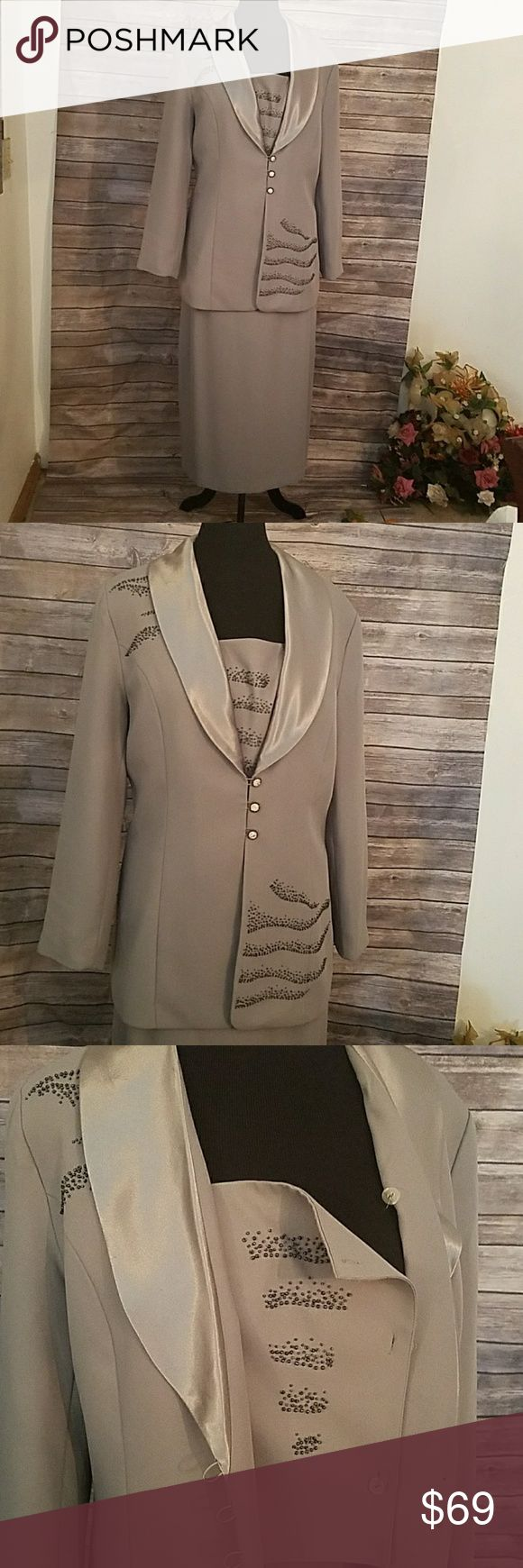 Nicole Studio Grey Two Piece Skirt Set 100% Polyester. Fully Lined.Dry Clean. Jacket has a detachable bib.Satin collar. 3 Rhinestone Button. Grey beads embedded throughout Jacket. The Skirt has a back zipper with one button. The Skirt has elastic side waistband and a back slit.Padded Shoulders Nicole Studio Skirts Skirt Sets