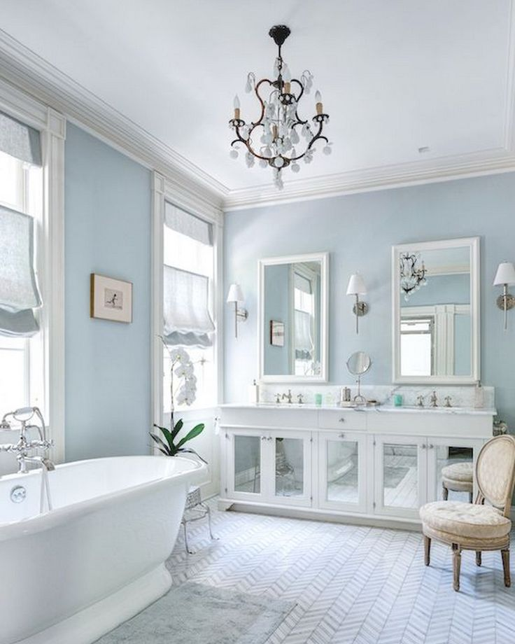 Master Bathroom:blue walls,chevron marble tile,blue bath rug,freestanding.pedestal bathtub,tub faucet with hand shower,French vanity chair,oval back vanity chair, white built in vanity with mirrored doors,marble counters, built in dual sink vanity,nickel cabinet pulls.