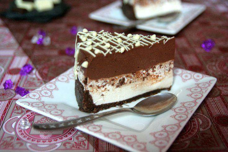 Crusta :250 g biscuiti digestivi cacao BelVita150 g unt topitCrema :400 g crema de branza250 g mascarpone150 g ricotta200 g zahar pudra1 lgt esenta de vanilie2 ml esenta de rom (1 fiola)200 ml frisca lichida50 g fulgi ciocolata neagra15 g gelatina granulata (1.5 plic)Crema ciocolata:200 ml frisca lichida100 g zahar160 g ciocolata neagra (75%cacao)2 lg cacao neagra70 ml coniac de buna calitateDecor :50 g ciocolata albaMod de preparare : Crusta : mixam biscuitii cu ajutorul robotului de…