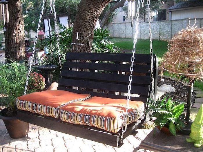 Schaukelgestell Aus Ketten Mit Orangen Kissen Und Eine Braune Bank Im Garten