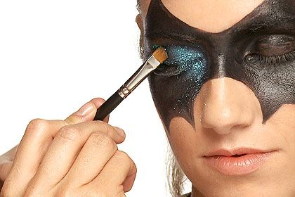 Step 2, Halloween Makeup Idea: Glamorous Mask Press Teal colored glitter on eyelids and along lower lash line