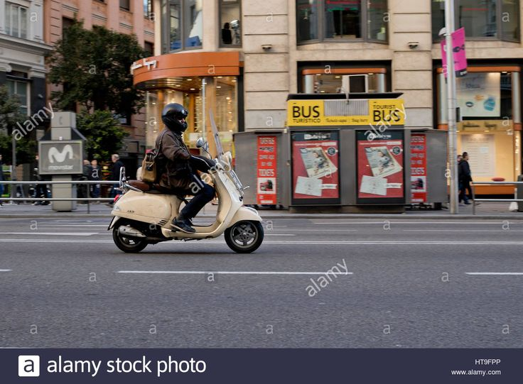 Download this stock image: One person riding a beige Vespa scooter motorcycle in Madrid city (Spain) 2017. - ht9fpp from Alamy's library of millions of high resolution stock photos, illustrations and vectors.