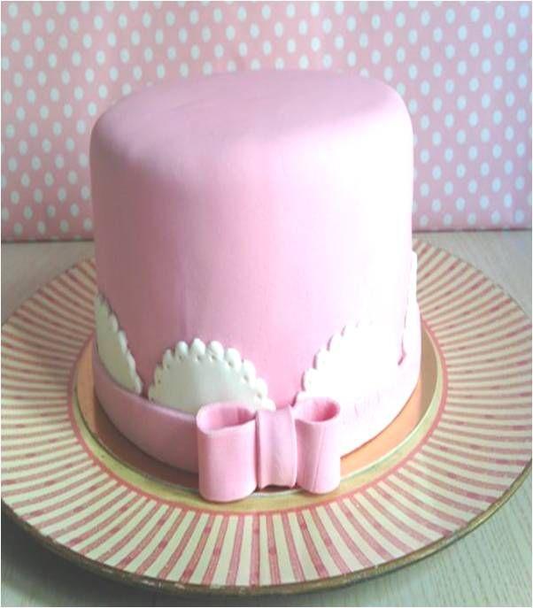Tarta de fondant rosa con ribetes y lazo para bautizo