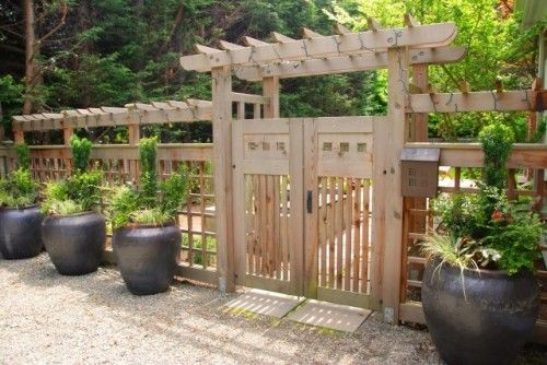 I like the use of urns to soften fence.  This see-through, Pagoda style fence would keep deer out and give climbing plants support