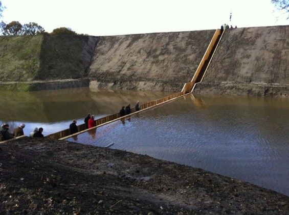 The Moses Bridge, Halsteren, The Netherlands. This sunken pedestrian bridge designed by RO & AD Architects parts the waters of the moat surrounding the 17th century Fort de Roovere. The walkway is carved into the landscape and steps lead down into the moat. The walls are built with Accoya (a very durable softwood hybrid) and lined with an EPDM foil waterproofing. A drainage system in the center of the path allows for overflow when water levels rise.