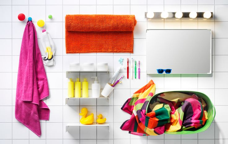 A collage image of colorful bathroom accessories, lighting and textiles displayed on top of square white tiles.