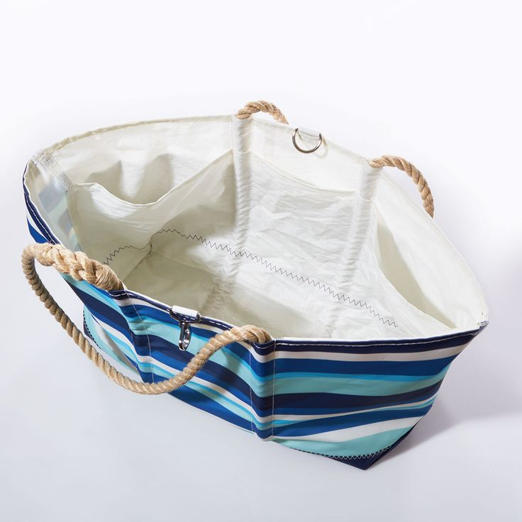 $195 SEABAGS~ Maine USA In colors that capture the depth changes in a tropical sea, this tote has two hidden features that make it the ideal sandy-beach bag: a back pocket for wet swimwear and a sand escape grommet so you don't bring the dunes home with you. This update on our popular swim tote has all the practical features you need-like a top clasp to keep things in place-in a fun new print. One side is two-tone in blue and white, the other features multicolor stripes.