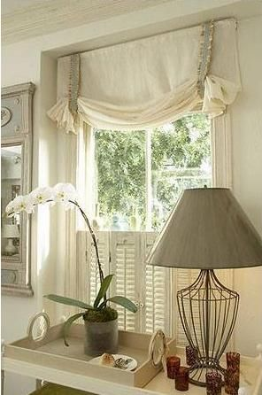 Roman shades done London swag style and cafe shutters. Love this combination - neutral colors in this cottage look. Budget Blinds of Benton
