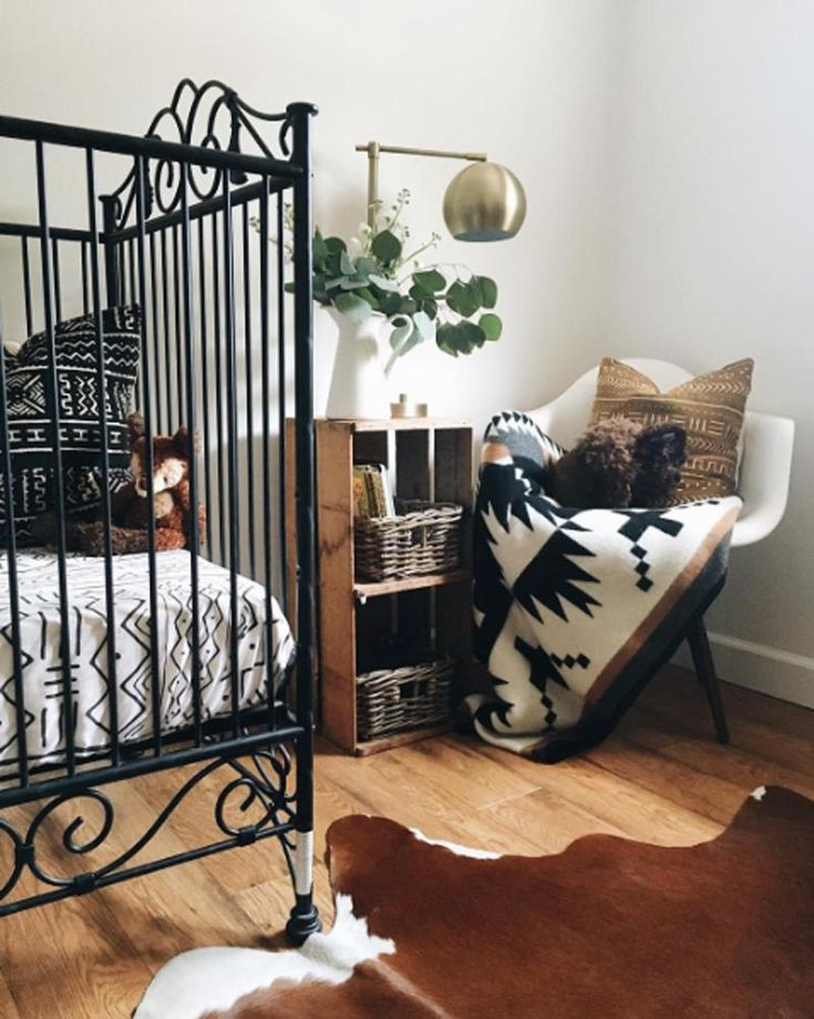 Love this chic nursery with southwestern notes.  The black iron crib is simple and drop dead gorgeous! #neutral #nursery