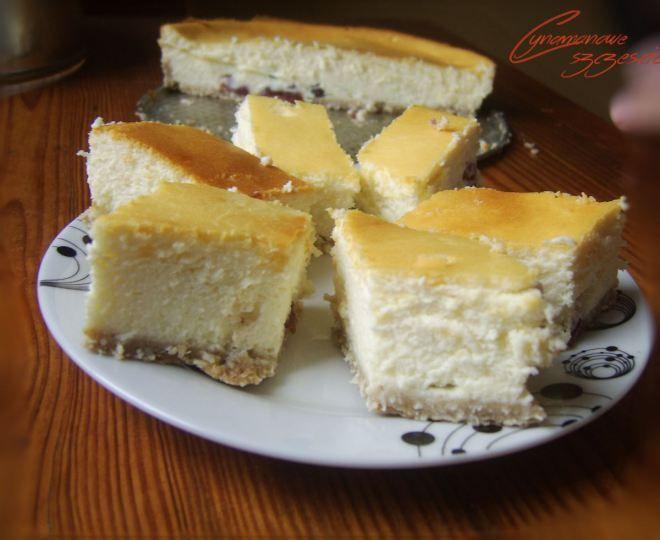 Delikatny sernik kokosowy  Spód:      2/3 szklanki mąki razowej     1/2 szklanki wiórek kokosowych     1 żółtko     2 łyżki masła     1 łyżka jogurtu naturalnego  Z podanych składników zagniatamy ciasto i wykładamy nim tortownicę o średnicy 22 cm  Masa serowa:      80 g masła     opakowanie cukru waniliowego     30 g cukru     3 jajka     200 ml mleka kokosowego     350 g sera na serniki     tabliczka białej czekolady     opcjonalnie suszona żurawina