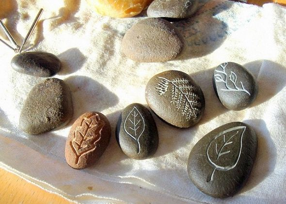 These beach pebbles were carved under running water using diamond bits in a Dremel tool, then beeswax was rubbed onto them to make the carvings more distinct