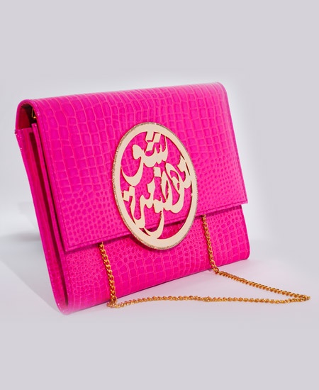 Fuchsia Hand- Made Glam Clutch made with 100% patent leather, gold-plated calligraphy plaque with Swarovski crystals and a gold chain.    The Glam Clutch is created by Palestyle a brand that works with Palestinian Refugee Women in camps in Jordon and Lebanon. Palestyle fuses the traditional Arabic heritage with contemporary fashion to bring you a trendy and chic collection.  The accessories are handmade in Lebanon and the calligraphic writings are inspirational messages by the refugee women.