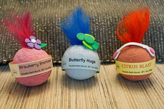 Not Hug Time, but Bath Time! Take a Troll-Inspired Fizzable Bath Bomb into the tub and it will fizz away to reveal a ring or necklace. Each piece of jewelry features one of the Troll characters. Depending on fragrance availability, the Troll-Inspired Bath Bombs come in Strawberry Shortcake