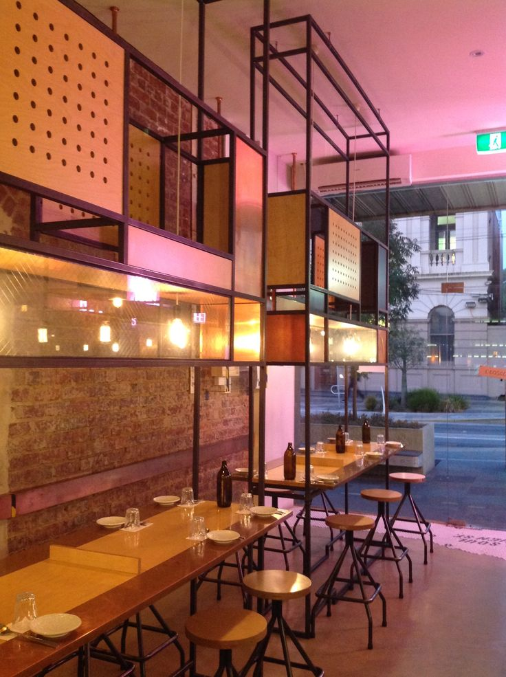 The Seoul Soul restaurant in High Street, Northcote uses steel square tubing frames extending from the door to the ceiling to house communal tables, giving the feel of sitting at an Asian food stall.  The metal frames are clad irregularly with copper and timber panels. The glass panels in the metal frames house hanging globes that provide soft light. Sheets of copper are also wrapped around the edges of the dining tables tying the scheme together.