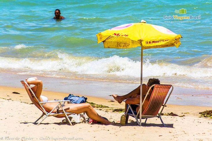 Imagem de casal tomando sol e a beira mar na Praia de Ponta Verde, em Maceió, Alagoas, Brasil.