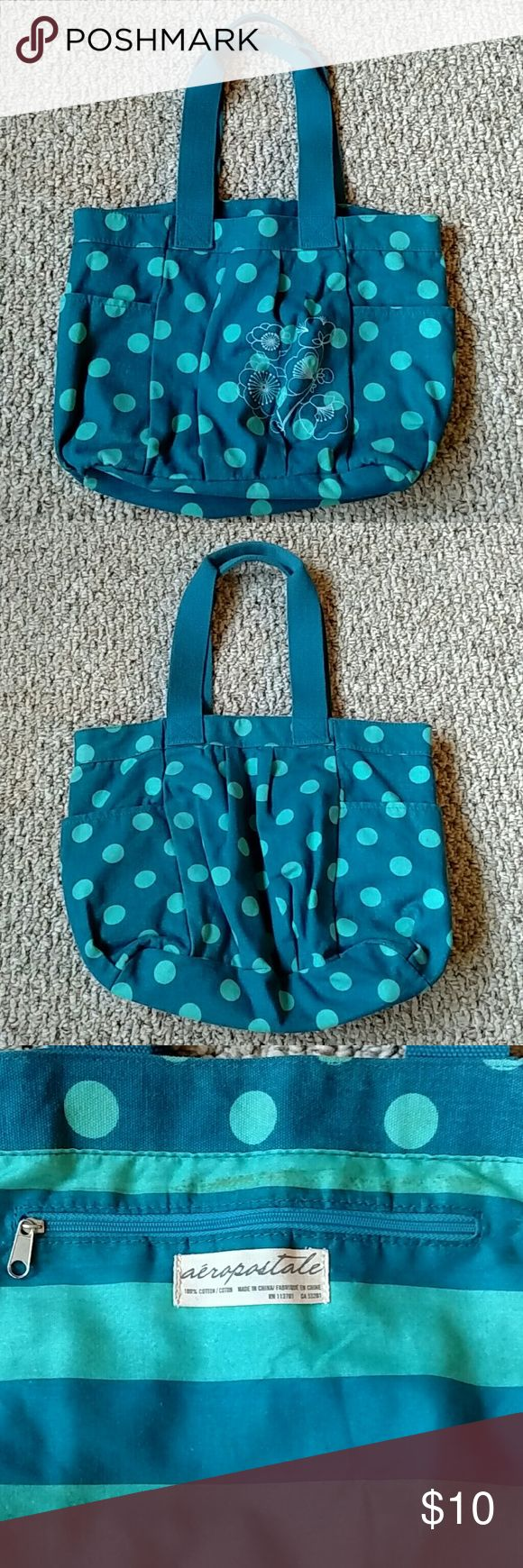 """Aeropostale Polka Dot Bag Used condition with some wear on the outside. Only major flaw is that the fabric around the zipper in the inside is discolored (pic 3 & 4). The material is canvas, blue with baby blue polka dots, and has a white floral embroidery on the front. It has an inside zipper pocket and 2 outside pockets. Length: 10"""" Width: 15"""" Depth: 5"""" Outside pockets: 7""""x 8"""" Strap Height: 9"""" Aeropostale Bags Shoulder Bags"""