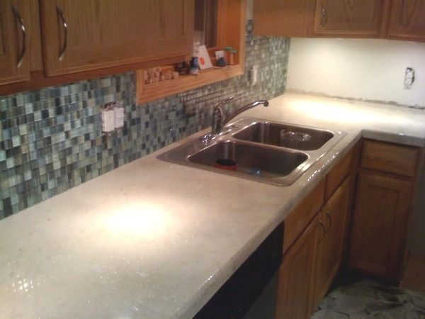 light wood cabinets and white concrete countertops but with a marble herringbone tile backsplash - Tijdelijke Backsplash