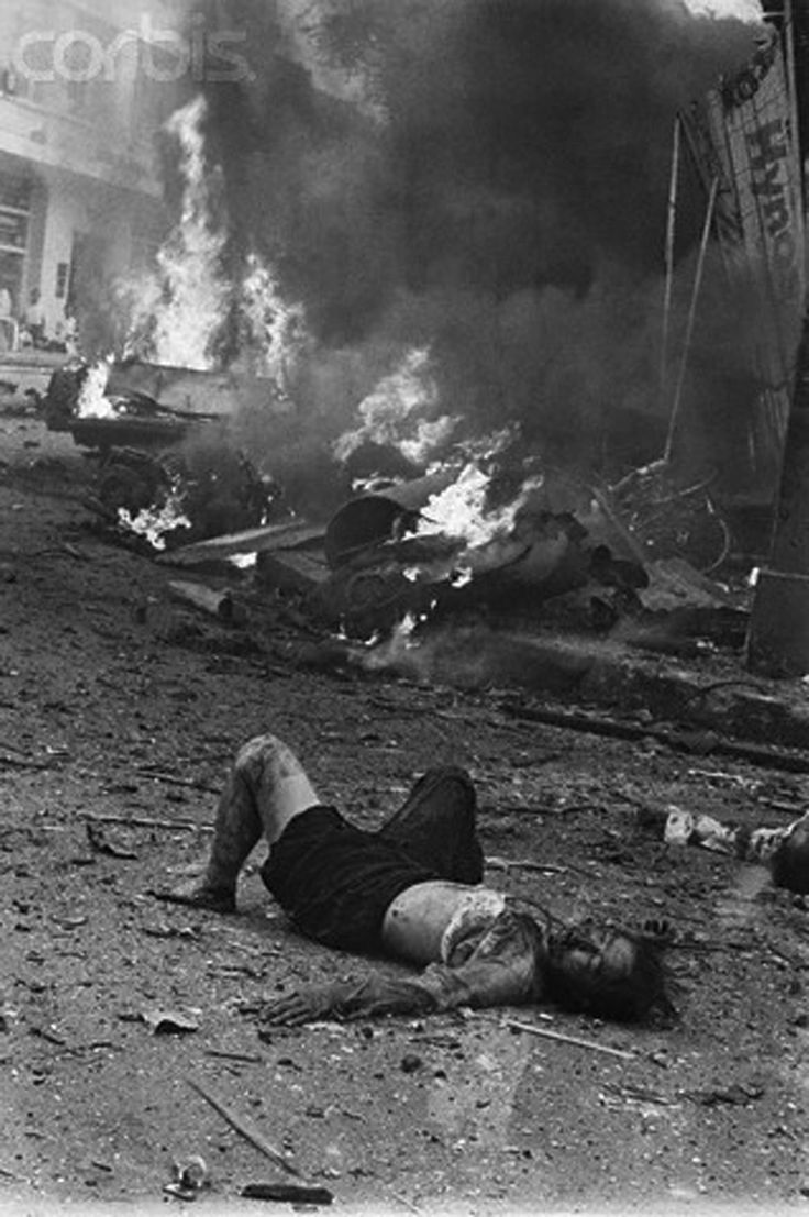 30 Mar 1965, Saigon, South Vietnam --- Saigon, South Vietnam: A dead woman lies among flaming debris of the American Embassy after a terrorist bomb rocked the building and surrounding area wounding and killing an estimated 50 persons