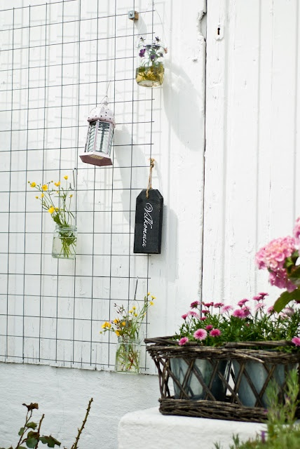 Obviously not as twee, but having a metal grid up on one of the outdoor walls could be useful for display/ flowers & echoes grid inside.