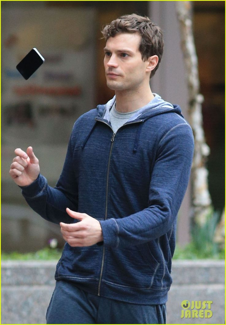 Jamie Dornan on set of Fifty Shades of Grey looking super good while messing around with his iPhone.