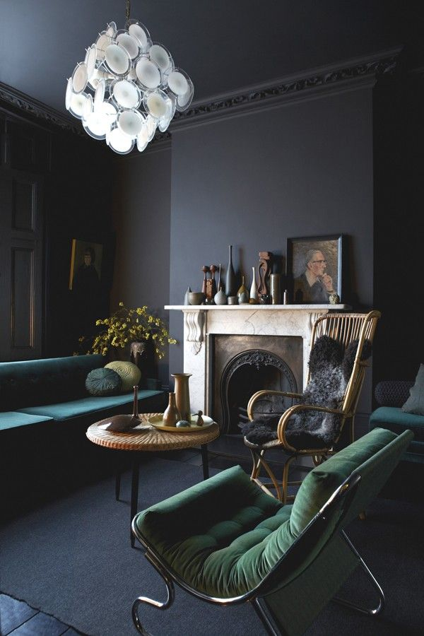 Living room with black walls and green furnishings. Milk Magazine