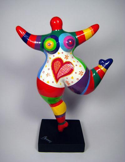 Biriney - Œuvres d'Art uniques inspiration Nicky de St Phalle C'est une madame pas de tête avec la jambe et les bras dans les aires.Ils y a plusieurs couleurs dont le rouge,bleu.mauve,vert et jaune. Quand je regarde l'œuvre je ressens de la surprise parce que la madame aussi a l'air surprise et de la joie à cause des couleurs. La madame a un cœur rouge sur le ventre. L'œuvre est probablement fait en argile. J'aime cette œuvre grâce aux couleurs qui la rendent joyeuse.