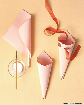 Martha Stewart Living, May 2001: Flower Cones How-To. To make flower cones, cut medium-weight paper into a 7-inch square. Use decorative scissors to scallop edge and a pencil to form tip. Secure outer flap of cone with craft glue. Punch six holes, 1 inch apart, beginning at top front center; thread 20-inch length of 1/2-inch-wide ribbon through holes. Tie bow at front, and leave a 7-inch loop at the back.
