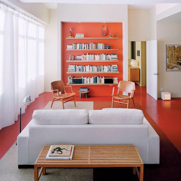 Idea soggiorno moderno minimal molto particolare. Il colore arancio rosso della pavimentazione in cemento viene utilizzato anche per il fondale della libreria