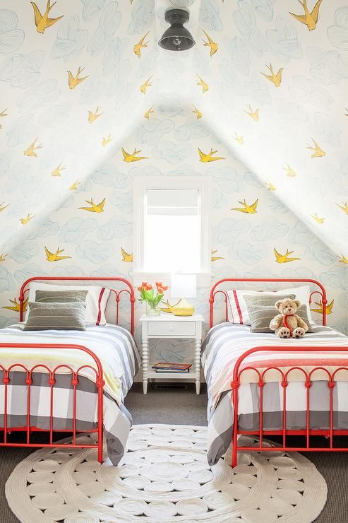 Contemporary shared attic kids' bedroom boasts a white round rug placed beneath two red twin metal beds dressed in gray gingham bedding accented with gray pillows and positioned on either side of a white spindle nightstand.
