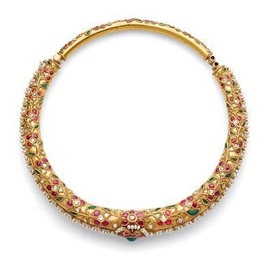 A hinged 'hasli' or collar necklace with a central stylised flower head, kundan-set with ruby and emerald cabochons and seed pearls, to a similarly designed surround of foliate motifs, kundan-set with rose-cut 'polki' diamonds, ruby and emerald cabochons, mounted in gold. Ca.. 1940s, Rajasthan