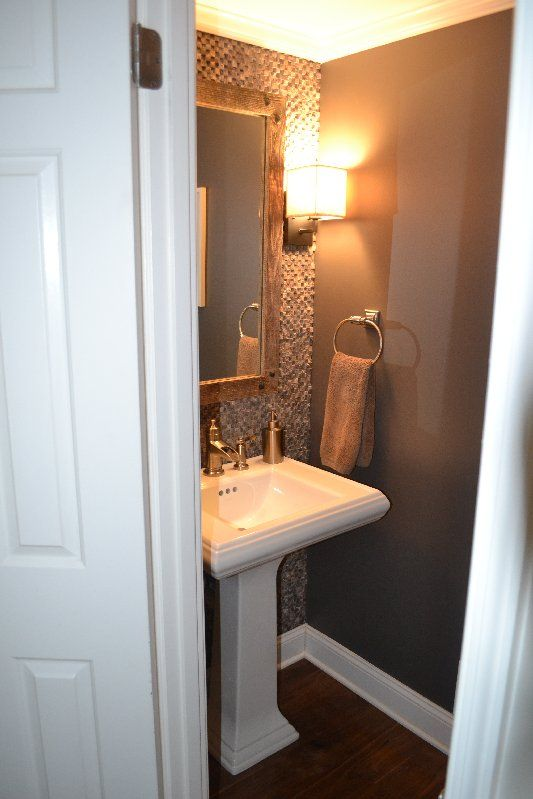 wall of tile in 1/2 bath- like to do this in main floor bath. Floor to ceiling tile on the wall with sink and toilet