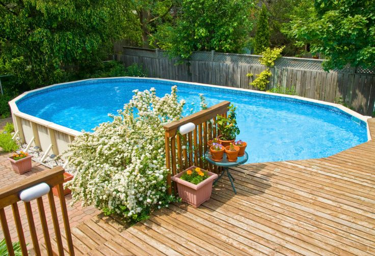 This raised deck sits on the far end of an oval above-ground pool. With a bit of landscaping, this above ground pool looks like an integral and permanent part of this yards design.