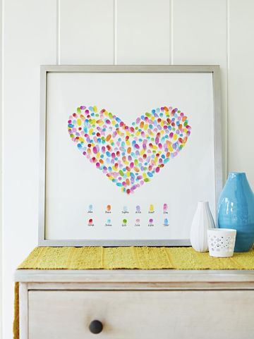We love this fingerprint heart gift idea! How it's done: Lightly pencil a simple shape onto a large piece of watercolor or other sturdy white paper (we made a heart, but a leaf, star, or tree is nice, too). Lightly trace a guideline or two below your drawing, then write guests' names along it with a marker. When family members arrive, ask them to choose a stamp-pad color and make scattered fingerprints inside the shape, as well as one just above their name. Then frame.