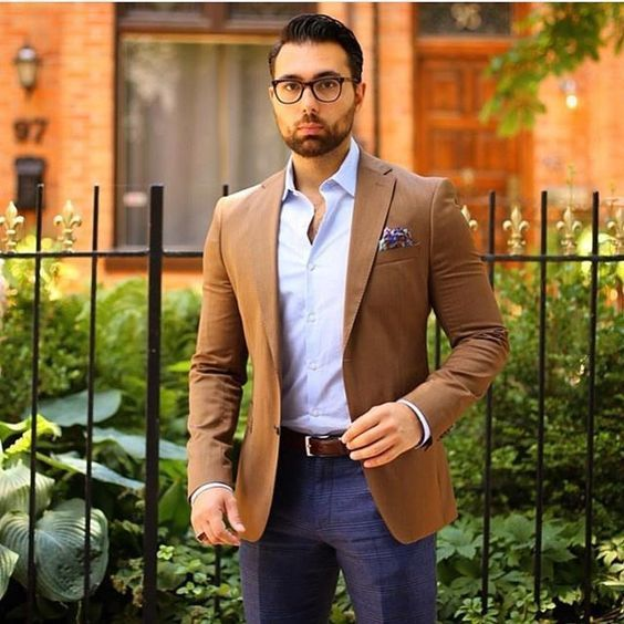 Tap into refined, elegant style with a camel sport coat and navy trousers.   Shop this look on Lookastic: https://lookastic.com/men/looks/blazer-long-sleeve-shirt-dress-pants/21081   — Light Blue Long Sleeve Shirt  — Violet Print Pocket Square  — Tan Blazer  — Brown Leather Belt  — Navy Dress Pants
