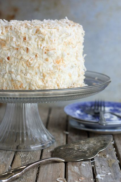 Southern Coconut Cake | Completely Delicious - the cake has coconut flavoring and coconut milk, and it is frosted with a cream cheese buttercream, and then covered in toasted coconut...yum!