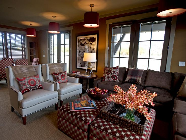 Inspired by a 19th-century saloon interior near the home's Park City, Utah location, this richly-colored transitional space is ready for lounging. Rows of red drum-shade pendants visually lower the ceiling, creating a feel of intimacy. Traditional wingback chairs, a sectional sofa and upholstered ottomans provide ample seating for a crowd.