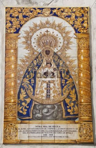 Large coat representing the Firmament, ornate colums and ornate blue and gold pattern on arch above her.  Tiled plaque of the Blessed Virgin Mary, Maria Virgen de Regla, on a sandstone church in the center of the Andalusian town of Chipiona, Spai...