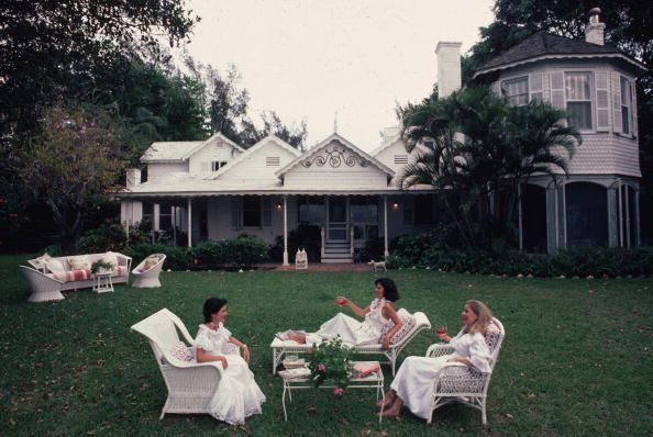 Circa 1982: Three women relaxing in front of a white clapperboard house in Palm Beach, Florida. Left to right, Hilda Juliette Arias de Rey Millet, Maria Victoria Herrera de Reynolds and Serina Bradley Martin Sanchez. Image by Slim Aarons