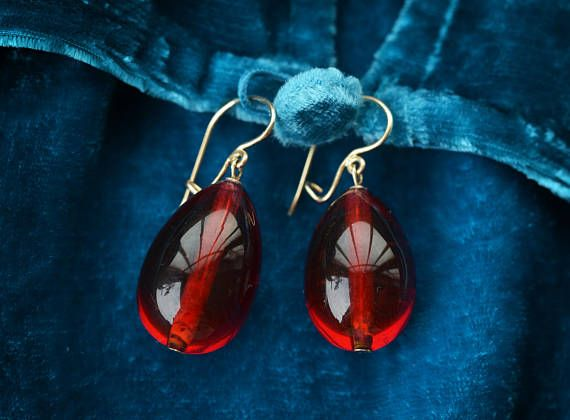 This is a rare antique 14 carat solid gold and amazing hot red crystal glass drop earring. This type of earwire was fashionable in the 1800s. The earwire closes safely. It is hallmarked for gold purity. I am not exactly sure of the exact age and where it was made. The crystals are hand