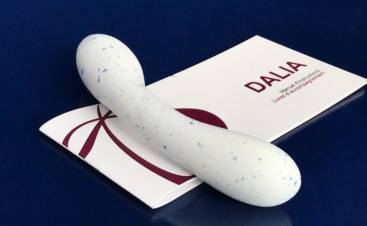 Special Edition of our porcelain intimate massager - the Dalia and its booklet- on a dark blue background